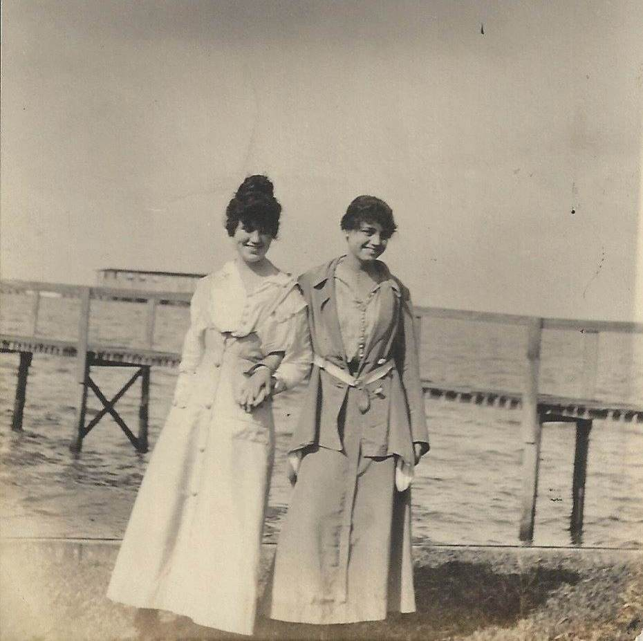2youngwomenonlandinfrontofpier